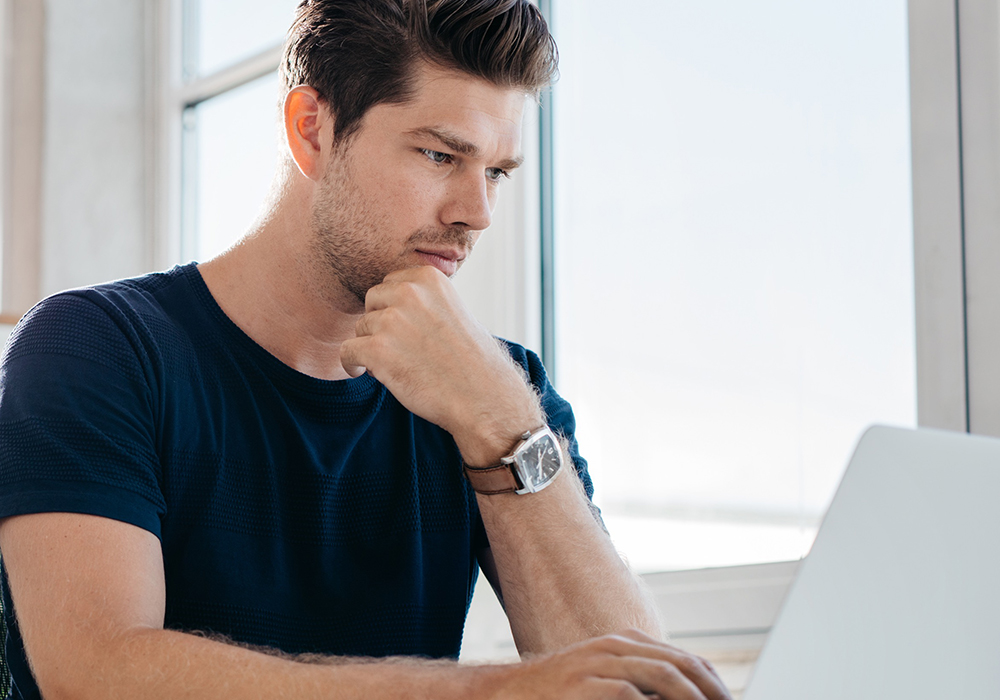 Male intensely staring at computer screen