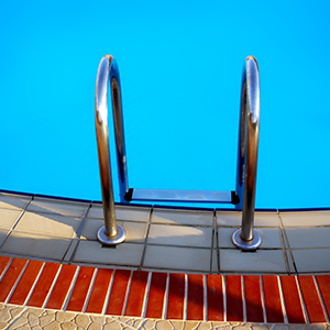 Clear blue swimming pool with silver ladder
