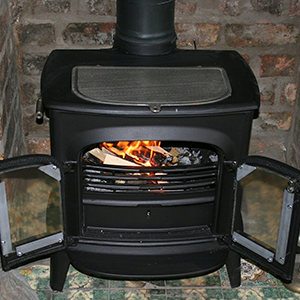 Small black wood burning fireplace with chimney